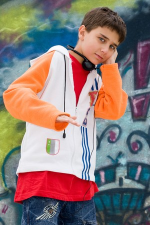 Teenager listening music against a graffiti wall Stock Photo - 4181672