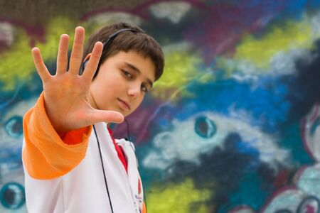 Cool teenager with his hand up, against a graffiti wall Stock Photo - 4181659