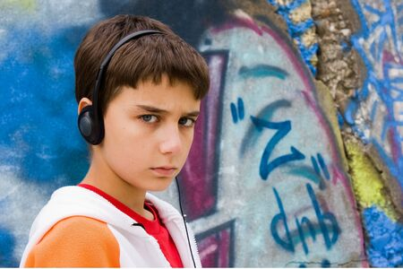 portrait of a cool teenager listening music against a graffiti background Stock Photo - 4181668
