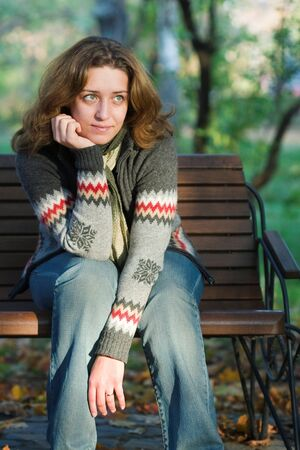 pretty woman sitting on a bench in park photo