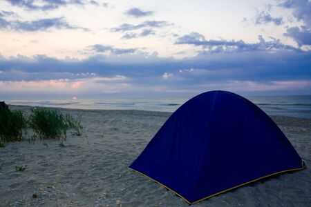 Blue tent on the beach at sunrise photo