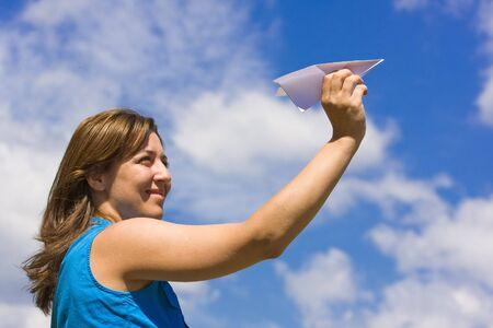 Girl launching  a paper plane photo