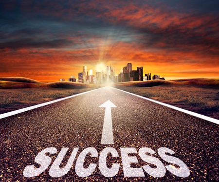 Empty asphalt road with success sign towards a city at sunset Stock Photo