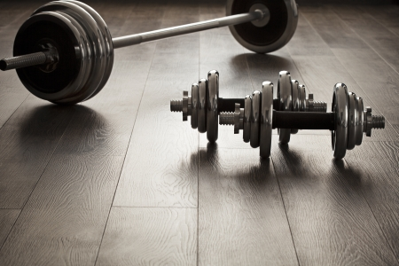 dumbells for fitness on wooden floor with empty space