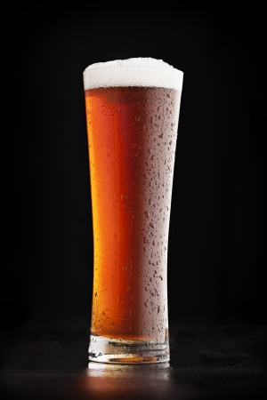 Glass of cold amber beer on a dark background