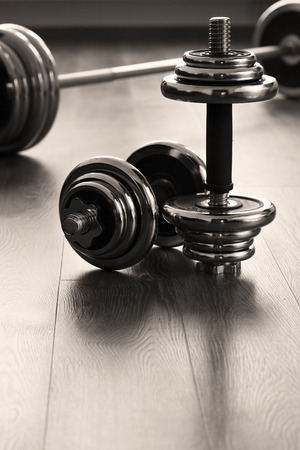 vertical dumbells for fitness on wooden floor Фото со стока