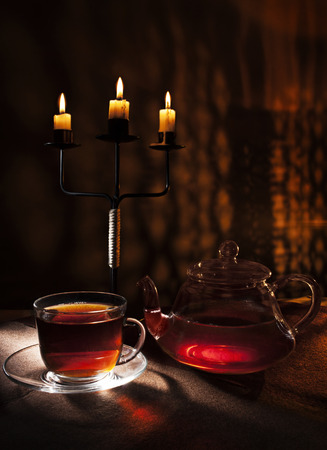 tea by candlelight with a reflection of the flames of the burning hearth