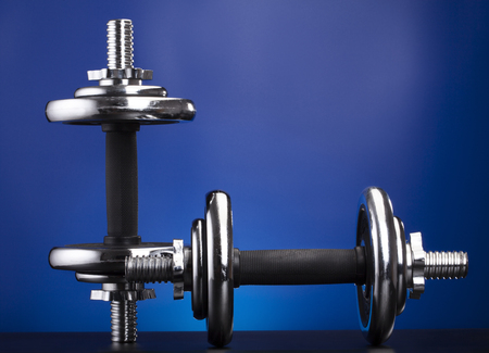 vertically and horizontally arranged dumbbell on a blue background