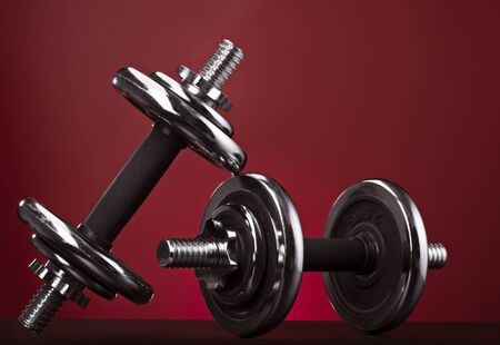 Contrasting shiny dumbbell on a red background 写真素材