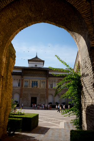 Seville, Spain - June 19: The real Alcazar, Seville, Spain on June 19, 2017. Tourists walking in the courtyard on a warm summer day.