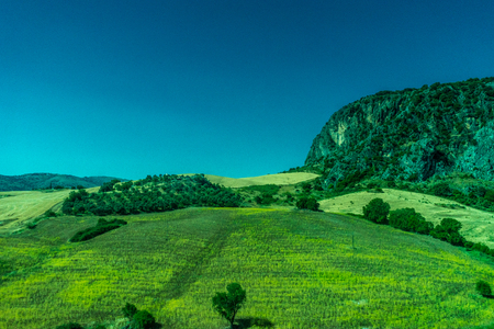 Greenery, Mountains, Farms and Fields on the outskirts of Ronda Spain, Europe on a hot summer day with clear blue skies