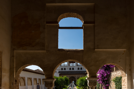 View of The Generalife courtyard, with its famous fountain and garden through an arch. Alhambra de Granada complex at Granada, Spain, Europe on a bright summer day