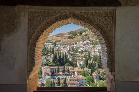 View of the Albayzin district of Granada, Spain, from a window in the Alhambra palace near sunset at Granada, Spain, Europe on a bright sunny day