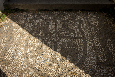 Shield patterns on a stone walking path at the Alhambra palace in Granada, Spain, Europe on a bright summer day