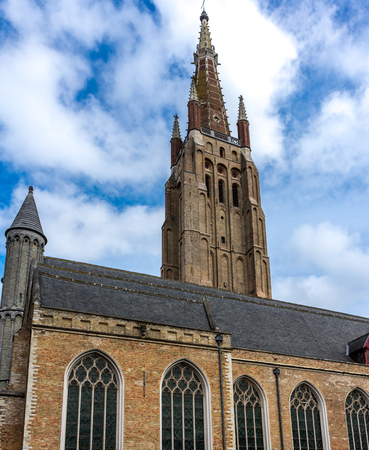 The Tower of the Church of our lady in Brugge, Belgium, Europe on a bright summer day with blue sky