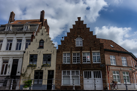 Brown, red and white Rooftop with gable and steps on the houses at Brugge, Belgium, Europe on a bright summer day with blue sky