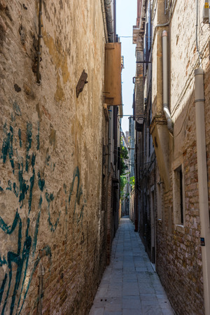 Europe, Italy, Venice, a narrow hallway with graffiti on the side of a building