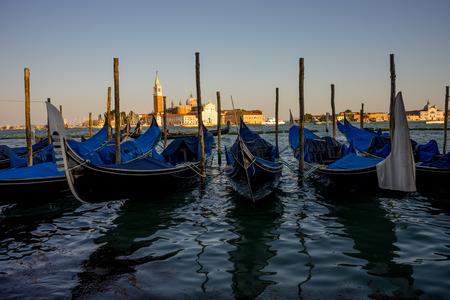 Venice, Italy - 30 June 2018: Gondolas moored by Saint Mark square with San Giorgio di Maggiore church in the background in Venice, Italy 報道画像