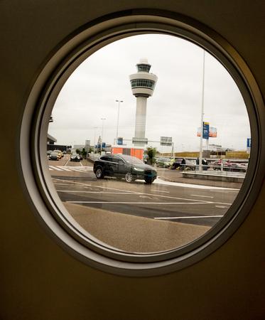 Amsterdam, Schiphol - 22 June 2018: The airport tower viewed through a circular glass window