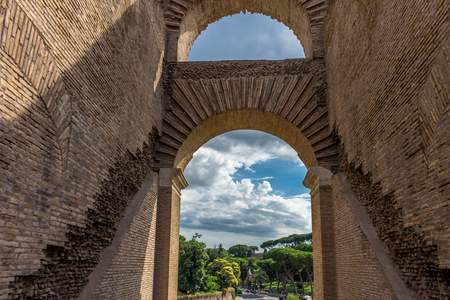 Rome, Italy - 23 June 2018: Ruins of the roman forum viewed through the gated arch of the passage at the entrance of the Roman Colosseum (Coliseum, Colosseo), also known as the Flavian Amphitheatre. Famous world landmark. Scenic urban landscape.