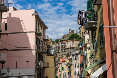 Riomaggiore, Cinque Terre, Italy - 26 June 2018: The cityscape of Riomaggiore with the clock tower in the background