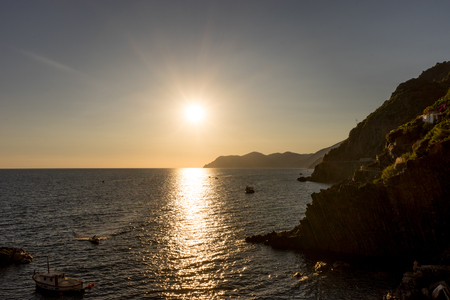 Golden sunset at the cliff at the Italian Riviera in the Village of Riomaggiore, Cinque Terre, Italy