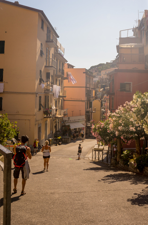 Riomaggiore, Cinque Terre, Italy - 27 June 2018: Tourists walking on the narrow streets of Riomaggiore