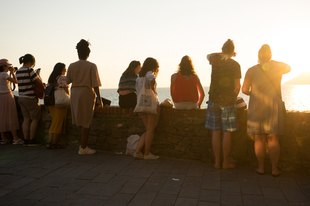 Riomaggiore, Cinque Terre, Italy - 26 June 2018: Toursists viewing the sunset at Riomaggiore across the ocean Stock Photo