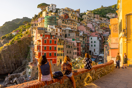 Riomaggiore, Cinque Terre, Italy - 26 June 2018: Toursists viewing the cityscape of Riomaggiore during the golden sunset hour