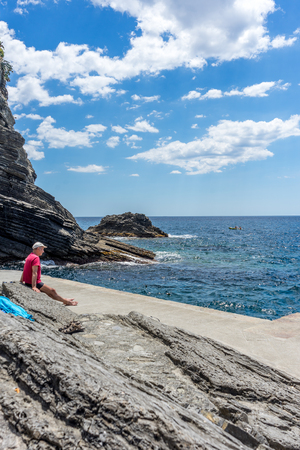 Vernazza, Cinque Terre, Italy - 26 June 2018: Tourist sitting on a rock overlooking the ocean at Vernazza, Cinque Terre, Italy