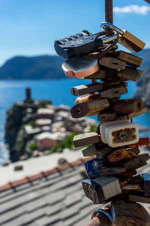 Vernazza, Cinque Terre, Italy - 26 June 2018: Close-up of padlocks against blue ocean at Vernazza, Cinque Terre, Italy
