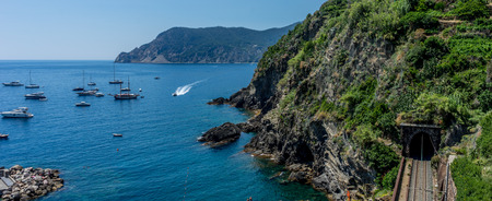 Europe, Italy, Cinque Terre, Vernazza, a small boat in a body of water with a mountain in the background Stockfoto