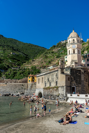 Vernazza, Cinque Terre, Italy - 26 June 2018: Tourists enjoying the beach and sunshine at Vernazza, Cinque Terre, Italy