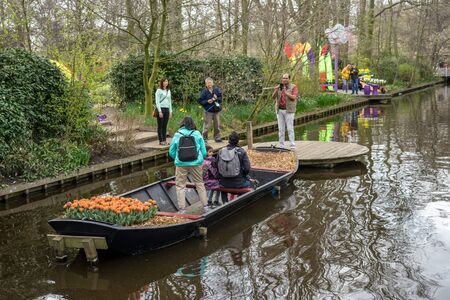Flower garden, Netherlands, Europe, San Antonio River Walk, a group of people in a boat on a river with San Antonio River Walk in the background