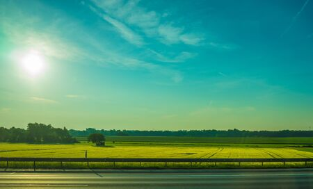 Germany, Frankfurt, Sunrise, Outkirts, a large long train on a lush green field