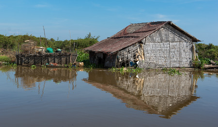 Ramshackle hut on the tranquil lake in Cambodian village