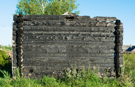 charred: Burnt charred log house. On a sunny day
