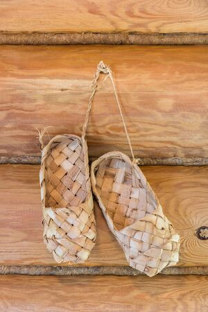 log wall: Bast shoes hanging on the log wall. Russian style Stock Photo