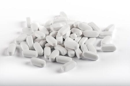 pilule: Muchas pastillas blancas sobre fondo blanco. Aislado