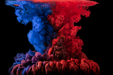Ink mixing together under water on black background. Red and blue