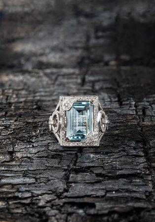 charred: Topaz ring. Blue stone rectangular shape on charred cracked board Stock Photo