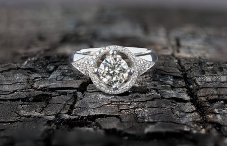 charred: Platinum diamond ring on black charred cracked board Stock Photo