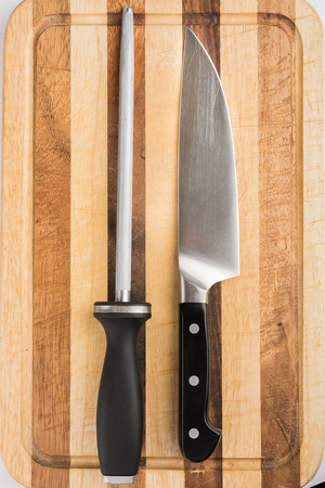 honing: Cooks knife and honing steel on wooden cutting board
