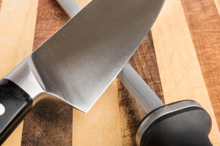 Kitchen knife and sharpening steel closeup on cutting board