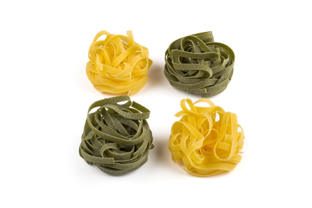 fettuccine: Tagliatelle pasta. Green and yellow. Dry fettuccine. Isolated on white Stock Photo