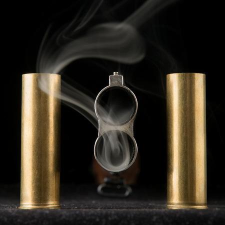 amendment: Smoking barrel of rifle and two shells on black background Stock Photo