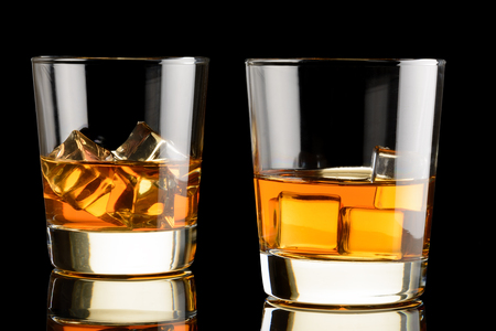 whiskey on the rocks: Two glasses of whiskey with ice on black background. Whisky on rocks