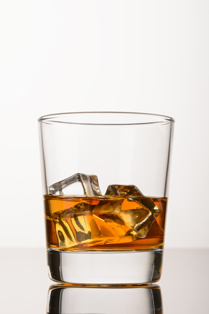 whiskey on the rocks: Whiskey on the rocks in the glass. Close up. Whisky with ice on white background Stock Photo