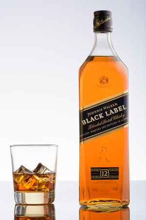 scotch whisky: Moscow, Russia. May 13, 2016. Black label. Johnnie walker. Blended scotch whisky. 12 years. Bottle and glass with ice. White background