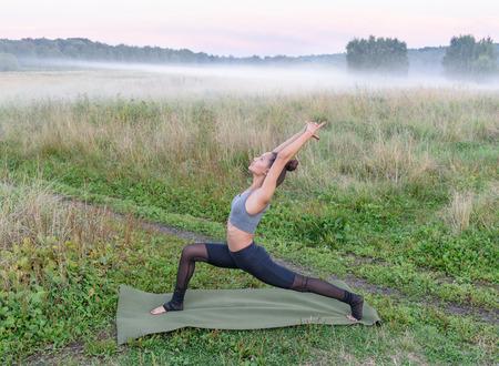 yogini: Yoga outside. Beautiful girl stands in virabhadrasana pose on misty field